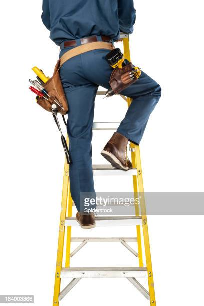 Handyman In Uniform And Tool Belt  Climbing Ladder