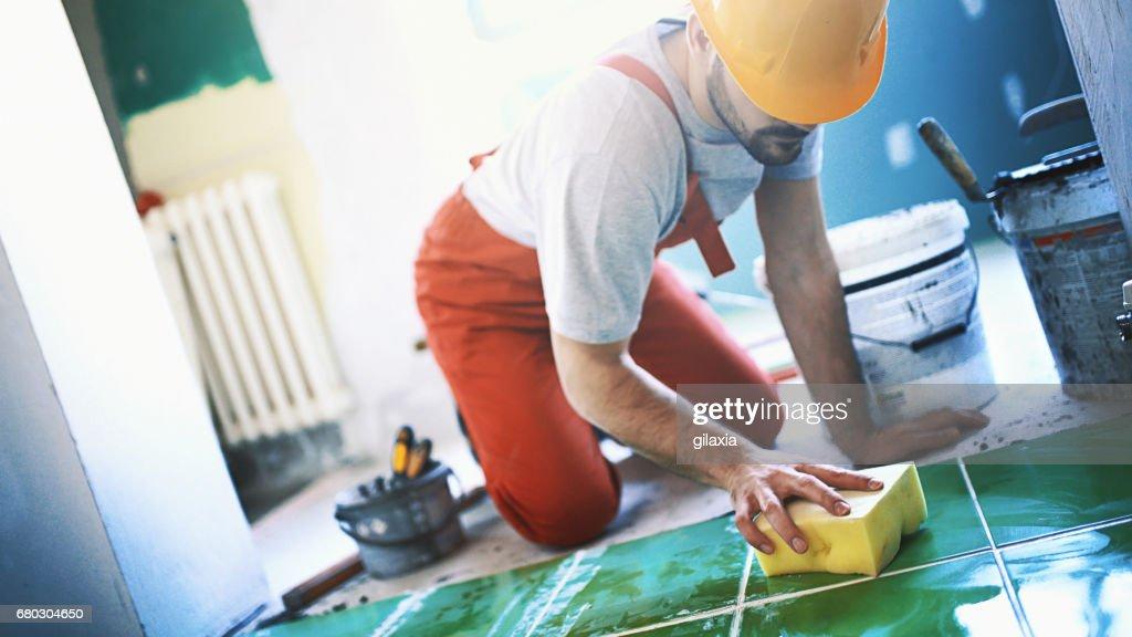 Handyman installing ceramic tiles. : Stock Photo