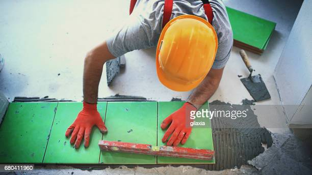 handyman installing ceramic tiles. - work glove stock photos and pictures