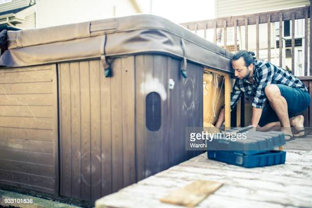 handyman repairing a hot tub - hot tub stock pictures, royalty-free photos & images