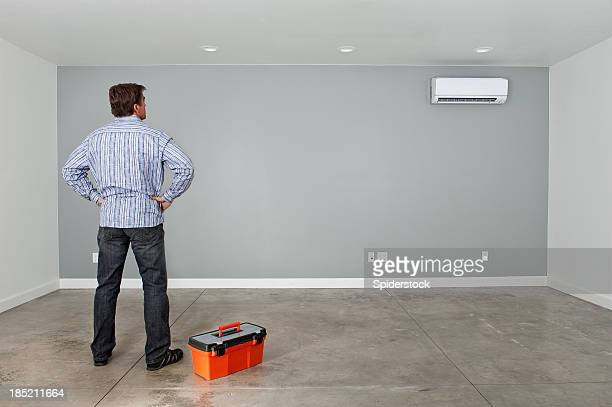 handyman standing in empty room - wainscoting stock photos and pictures