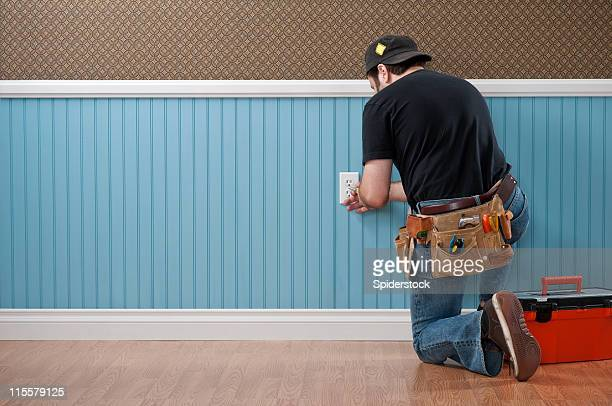 handyman working in empty room - electrician stock pictures, royalty-free photos & images