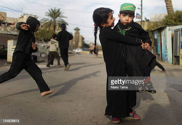 Haneen Muaid holds her brother Aiad Muaid outside Seid Idrees mosque on the day before the festival Ashura on December 5 2011 in Baghdad Iraq Ashura...