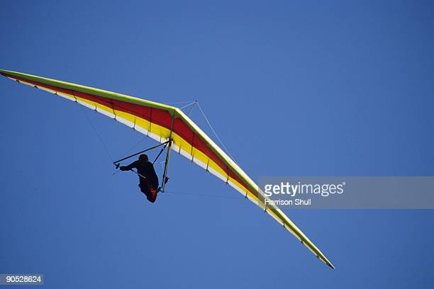 Hang glider banks into a turn against a blue sky.