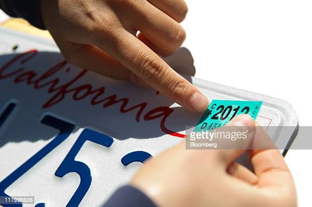 Hang Nguyen of San Francisco applies a 2012 registration sticker to her license plate at the Department of Motor Vehicles in Daly City California US...