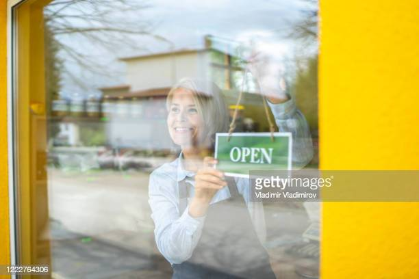 hanging a shop opening sign - reopening stock pictures, royalty-free photos & images