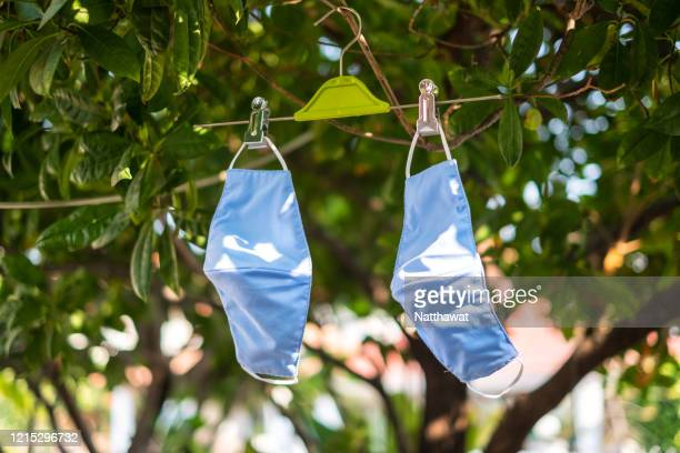 hanging and drying fabric face masks in the sun - masque tissus photos et images de collection
