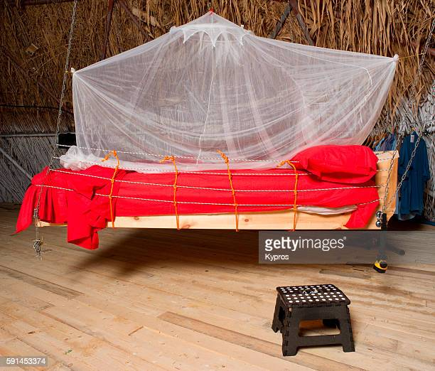 hanging bed with mosquito net and red sheets - mosquito net stock photos and pictures