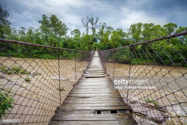 hanging bridge over mountain river - hängebrücke stock-fotos und bilder