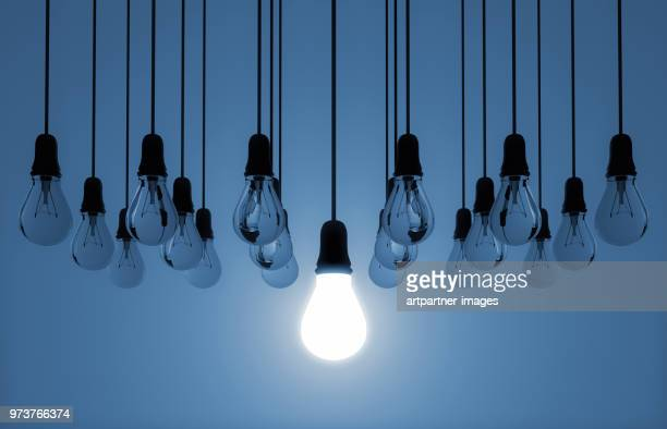 hanging light bulb switched on - inspiration stock-fotos und bilder