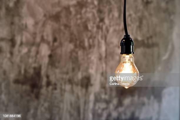hanging light bulbs against a concrete wall - pendant light stock pictures, royalty-free photos & images
