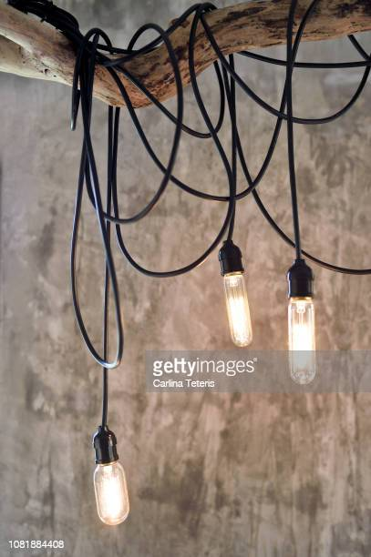 Hanging light bulbs against a concrete wall