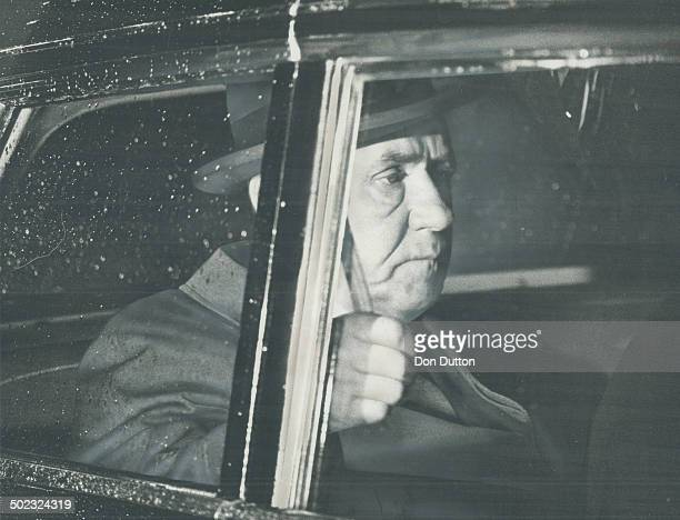 Hanging on tight to the handstrap in the rear seat of his limousine visiting Soviet Premier Alexei Kosygin rides through the rain last night from...