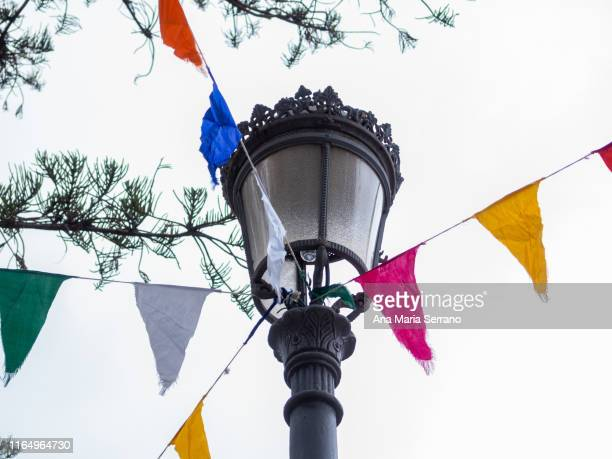 hanging party banners of various colors for decoration with cloudy sky - fiesta al aire libre fotografías e imágenes de stock