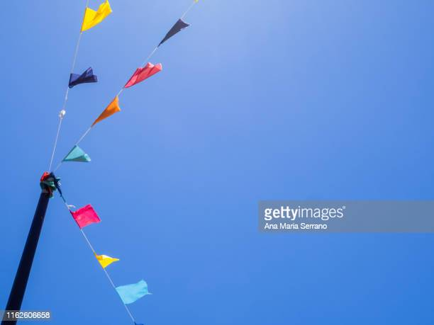 hanging party flags of various colors for decoration with the clear sky - fiesta al aire libre fotografías e imágenes de stock