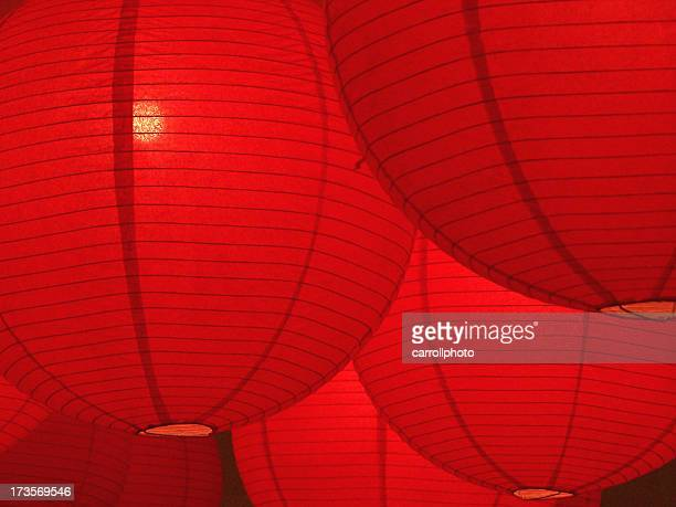 hanging red paper lanterns glowing - lantern stock photos and pictures