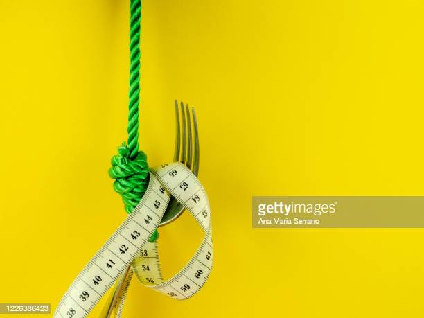 a hangman's knot, a fork and a tape measure on a yellow background. eating disorder concept - hanging gallows stock pictures, royalty-free photos & images