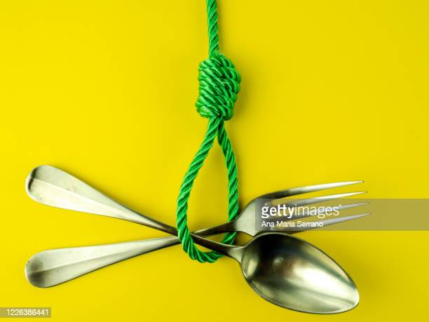 a hangman's knot, a spoon and a fork on a yellow background. eating disorder concept - hanging gallows stock pictures, royalty-free photos & images