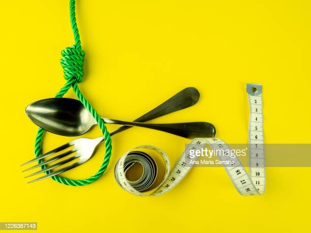 a hangman's knot, a tape measure, a spoon and a fork on a yellow background. eating disorder concept - hanging gallows stock pictures, royalty-free photos & images