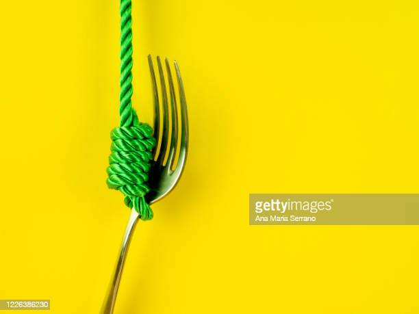 a hangman's knot and a fork on a yellow background. eating disorder concept - hanging gallows stock pictures, royalty-free photos & images