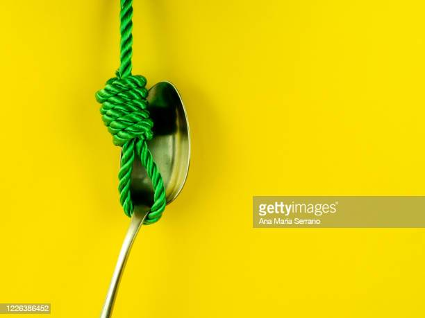 a hangman's knot and a spoon on a yellow background. eating disorder concept - hanging gallows stock pictures, royalty-free photos & images