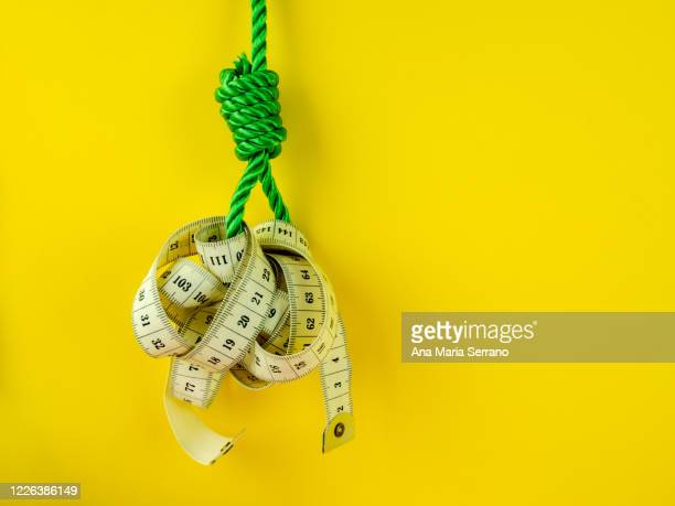 a hangman's knot and a tape measure on a yellow background. eating disorder concept - hanging gallows stock pictures, royalty-free photos & images