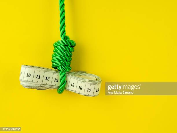 a hangman's knot and a tape measure on a yellow background. eating disorder concept - anorexia nervosa stock pictures, royalty-free photos & images