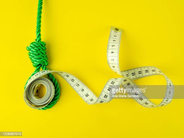 a hangman's knot and a tape measure on a yellow background. eating disorder concept - bulimia fotografías e imágenes de stock
