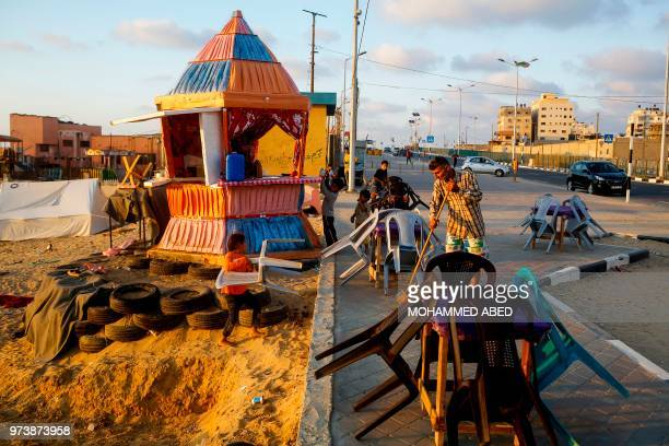 TOPSHOT Hani alLaham an employee of the Ramallahbased Palestinian government sweeps the street outside a coffee kiosk near the beach in Gaza City on...