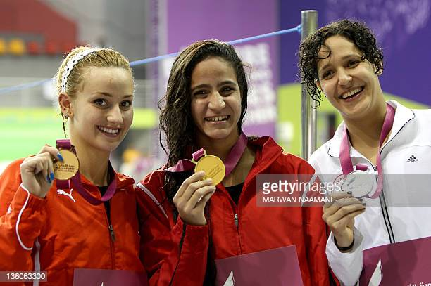 Hania Moro of Egypt poses with her gold medal of the women's 200m backstroke along with silver medalist Sarra Lajnef of Tunisia and bronze medalist...