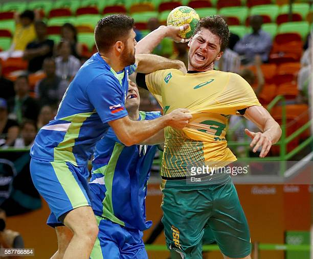 Haniel Langaro of Brazil tries to take a shot against Slovenia on Day 4 of the Rio 2016 Olympic Games at the Future Arena on August 9, 2016 in Rio de...