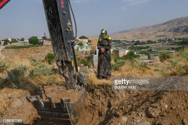 Hanife Ekinci 55yearsold waits next the grave of her fatherinlaw as a digger works to uncover the body which will be moved to the new Hasankeyf...