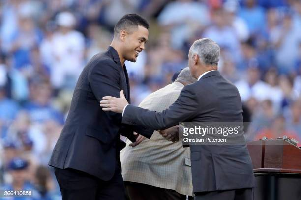 Hank Aaron Award recipient Giancarlo Stanton of the Miami Marlins shakes hands with Major League Baseball Commissioner Robert D Manfred Jr before...