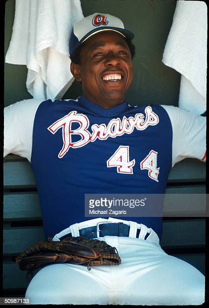 Hank Aaron of the Atlanta Braves smiles as he sits in the dugout in 1973