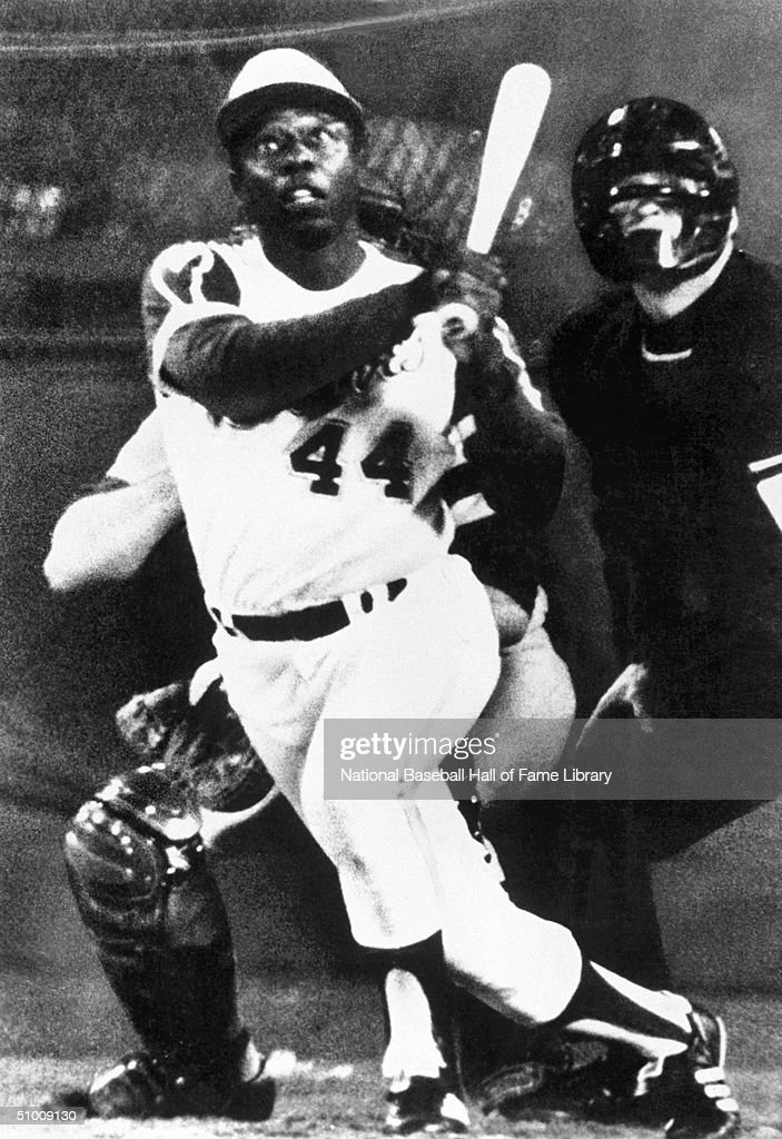 Hank Aaron #44 of the Atlanta Braves watches the flight of the ball after the swing during a game. Aaron played in Atlanta for the Braves from 1966-1975.