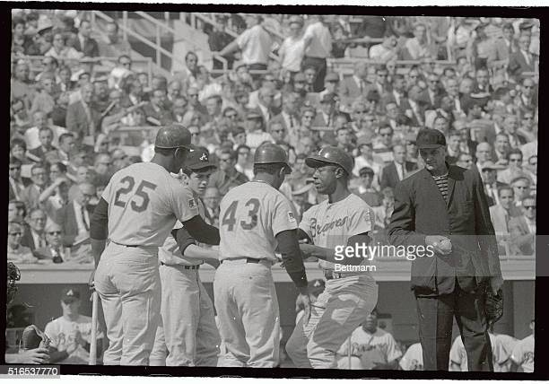 Hank Aaron of the Braves is congratulated at home plate by Rico Carty and Tony Gonzalez after hitting a two run homer in the first inning of the game...