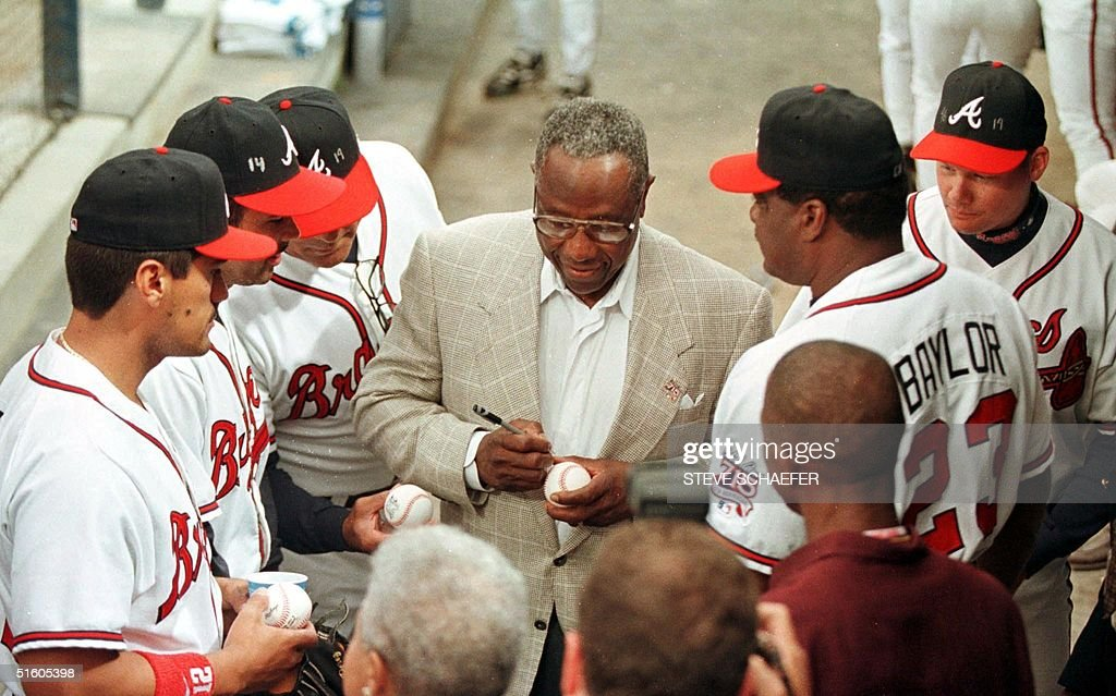 Hank Aaron (C) signs autographs for some of the Atlanta Braves players before ceremonies that unveiled the Hank Aaron Award on the 25th anniversary of his historic 755th home run 08 April 1999. The Hank Aaron Award will be based on the player's combined numbers of hits, home runs and RBI and is scheduled to be presented to the best hitter in each league Championship Series.