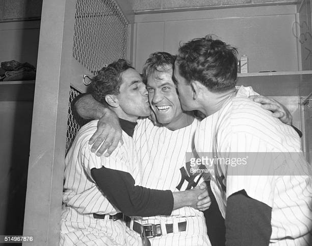Hank Bauer of the New York Yankees gets kisses from teammates Phil Rizzuto and Yogi Berra after Yanks defeated the Giants 43 in today's game to win...