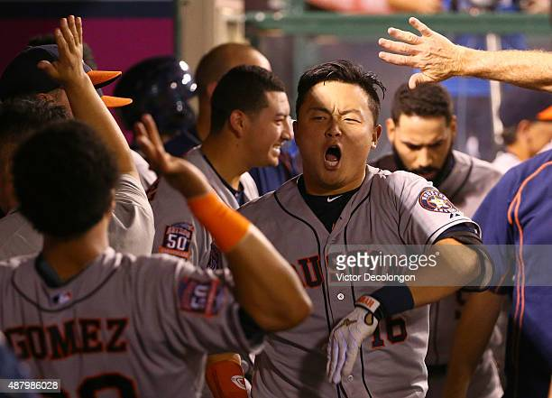 Hank Conger of the Houston Astros celebrates in the dugout with teammates after hitting a solo homerun in the seventh inning during the MLB game...