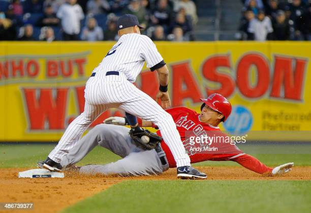 Hank Conger of the Los Angeles Angels of Anaheim slides into second base with a second inning RBI double under the tag of Derek Jeter of the New York...