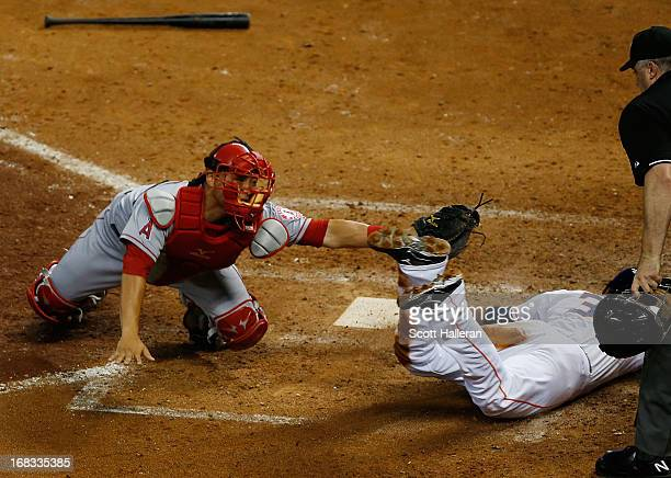 Hank Conger of the Los Angeles Angels of Anaheim tags out Jimmy Paredes of Houston Astros at home plate with umpire Bill Welke looking on in the...