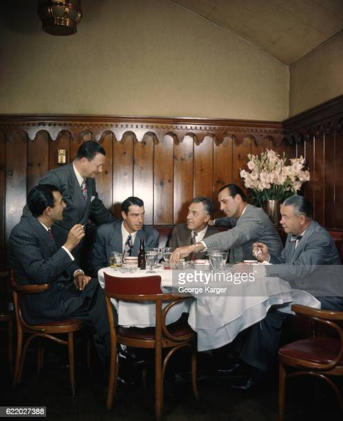 Hank Greenberg and Bob Feller with a group of men at a table at Toots Shor's Restaurant in New York City