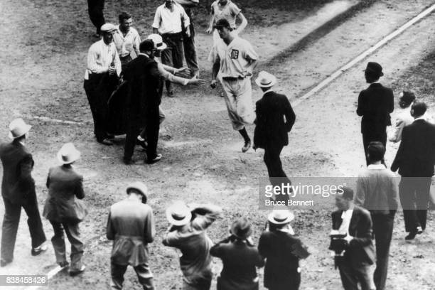 Hank Greenberg of the Detroit Tigers scores after hitting his second homerun of the game as photographers surround home plate circa 1934 at Briggs...