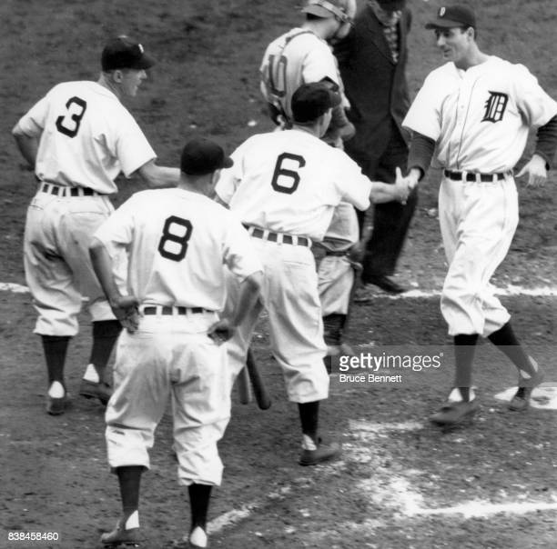 Hank Greenberg of the Detroit Tigers scores as he is congratulated after hitting a grand slam by teammates Eddie Mayo Roy Cullenbine and Roger Cramer...