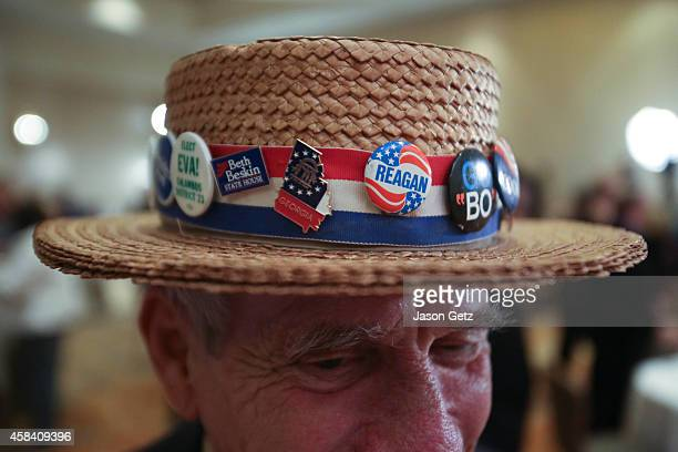 Hank Schwab of Atlanta shows the campaign hat he's worn for the past 30 years at a gathering in support of Republican US Senate candidate David...