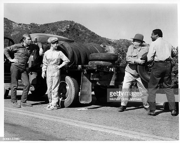 Hank Williams Jr Ed Begley and D'Urville Martin borrow a tire from Shelley Fabares in a scene from the movie A Time to Sing circa 1968