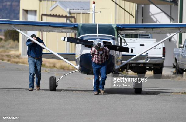 Hank Williams left and Ward Priestley right push and pull Williams' Cessna out of a hanger at the Nucla Hopkins Airport October 19 2017 Williams...