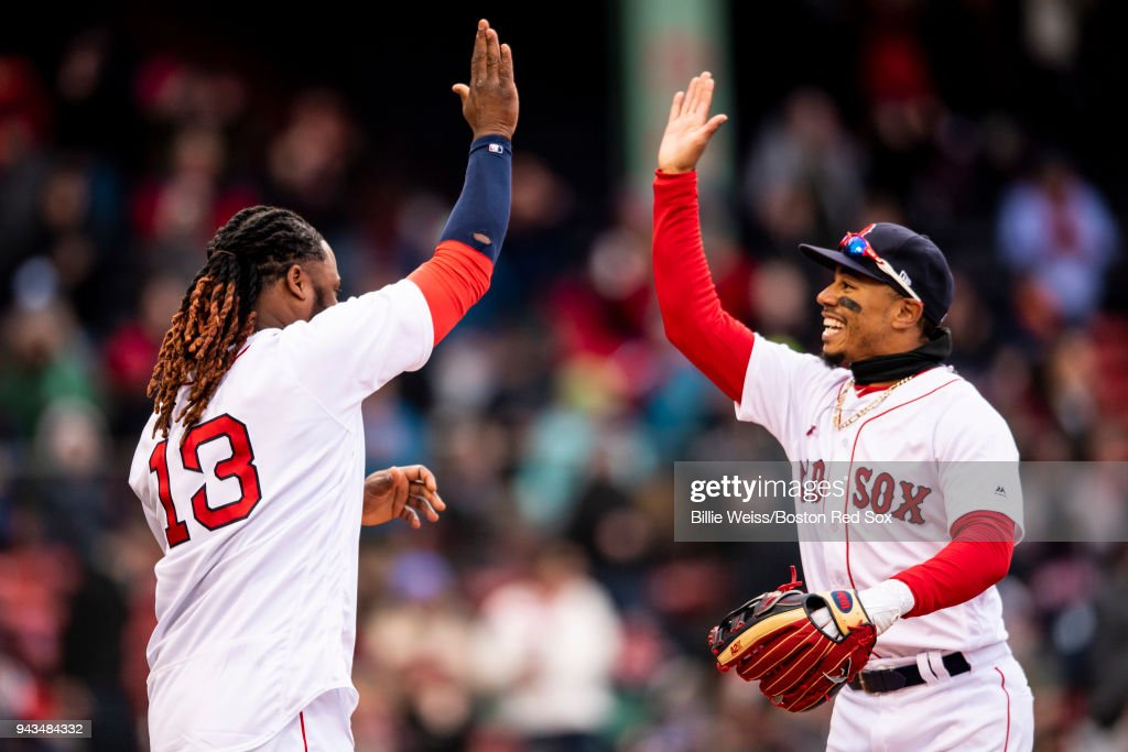 Hanley Ramirez #13 and Mookie Betts #50 of the Boston Red Sox celebrate a victory against the Tampa Bay Rays on April 8, 2018 at Fenway Park in Boston, Massachusetts.