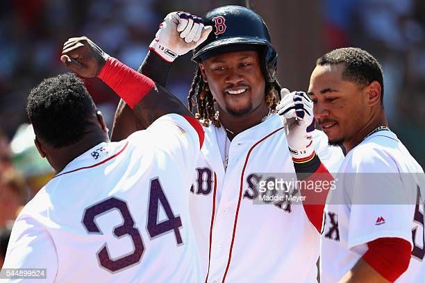 Hanley Ramirez of the Boston Red Sox celebrates with David Ortiz and Mookie Betts after scoring a run against the Texas Rangers during the third...