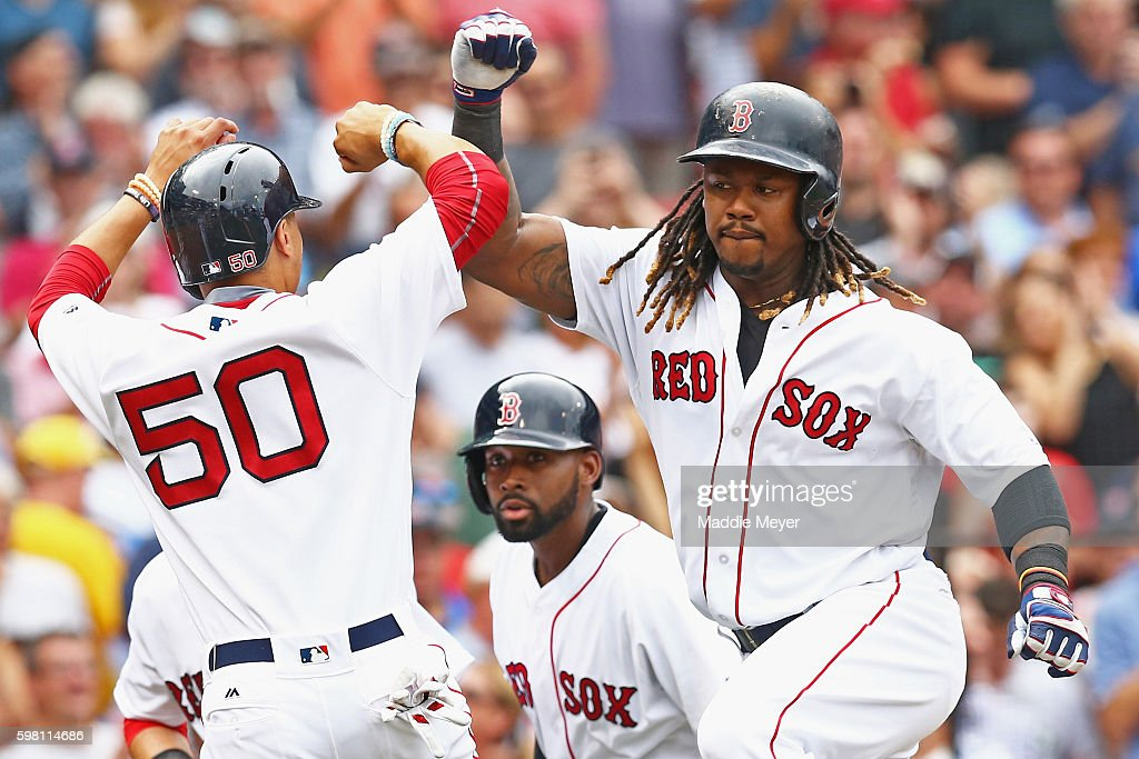 Hanley Ramirez #13 of the Boston Red Sox celebrates with Mookie Betts #50 after hitting a grand slam during the fifth inning against the Tampa Bay Rays at Fenway Park on August 31, 2016 in Boston, Massachusetts.
